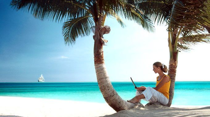 Woman on Tropical Beach with Laptop Computer
