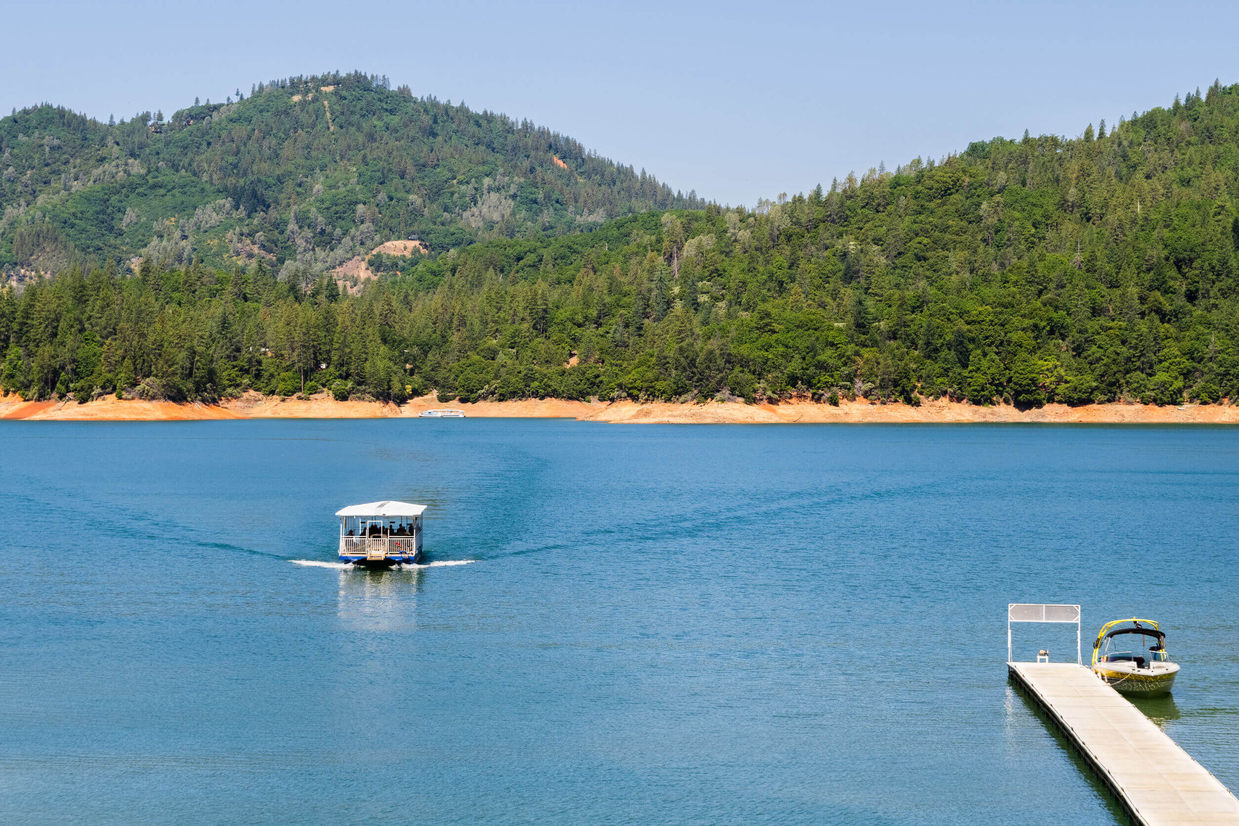 Shasta Lake, McCloud River Arm landscape on a sunny summer day with ship approaching the shoreline, Northern California